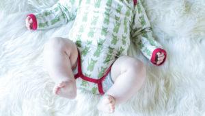 Baby, Säugling mit Body und nackten Beinen auf Fell liegend