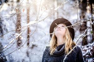 Junge Frau mit blonden Haaren winterlich bekleidet, Blick nach oben gerichtet