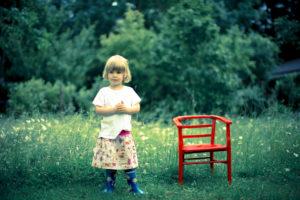 Mädchen steht auf einer Wiese neben einem roten Kinderstuhl