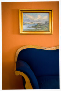 Old dark blue sofa, old oil painting with golden frame, orange-coloured wall