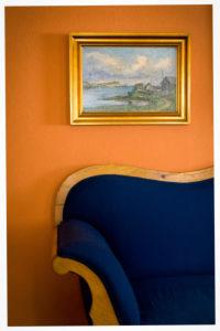 altes Sofa in dunkelblau, altes Ölbild mit goldenem Rahmen, Orange Wand