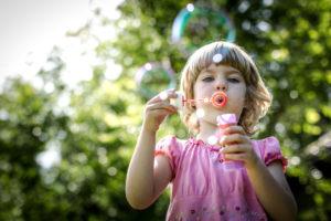 blondes Mädchen im rosa Kleid pustet Seifenblasen