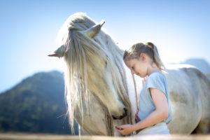 Pferd und Mädchen mit blonden Haaren