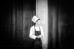 Chef, young man with chef's hat and apron, smiling, door in the background, black and white photo