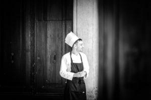 Koch, junger Mann mit Kochmütze und Schürze steht vor einer Tür und lächelt, schwarz-weiss Aufnahme