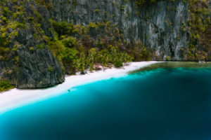 El Nido, Palawan, Philippines. Aerial drone view of solitude tropical hut on Pinagbuyutan Island. Amazing white sand beach with turquoise blue lagoon water.