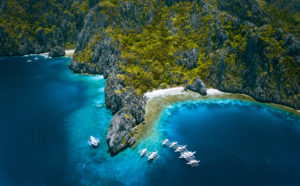 El Nido, Palawan, Philippines. Aerial view of Miniloc Island with diving boats above coral reef surrounded by karst limestone rugged mountain cliffs.