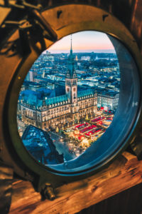 Top view of illuminated Christmas market on townhall square in advent time, Hamburg, Germany. Porthole window framed view.