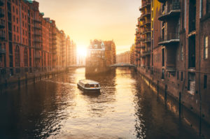 Hamburg warehouse district in golgen hour sunset lit. Water castle palace and tourist visting boat trip in river. Old warehouse port, Germany, Europe.