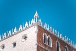 Piazza San Marco Saint Mark Square with Basilica di San Marco. Roof architecture details against blue sky in Venice,Italy. Tourist attraction, summer city trip.