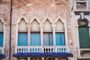 Facade of old house with windows on the street in Venice Italy.