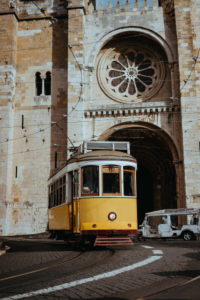 Quaint yellow tram passes directly in front of the Se Cathedral in Lisbon, Lisboa, Lissabon, Portugal, Europe