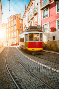 Touristic vintage red tram in a Lisbon street on sunny afternoon, narrow streets, cobblestones winding road, vacation in Lisbon