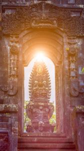 Gate in Pura Besakih Temple temple with Hindu Altar in sun light flares.