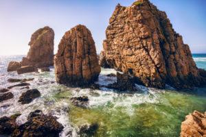 Ursa beach, Sintra, Portugal. Epic sea stack rocks rising from atlantic ocean in sunset light.