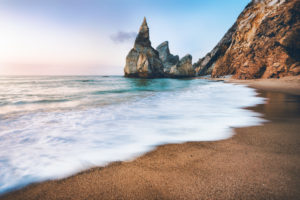 Portugal Ursa Beach. Sea stacks, white ocean wave lit by sunset light.