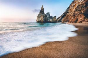 Portugal Ursa Beach. Sea stacks, white ocean wave lit by sunset light.