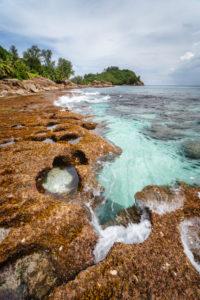 Old reef coastline and ocean waves on tropical Police Bay beach on Mahe Island, Seychelles.