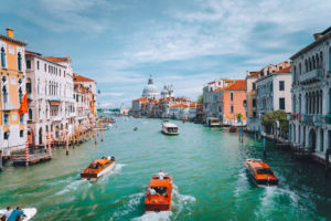 Venice, Italy. Tourist boats in Grand Canal with Basilica Santa Maria della Salute view in background.