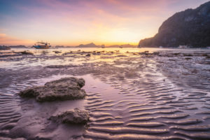 Corong beach, El Nido, Philippines. Sunset on tropical beach. Sun reflections at the golden hour. mountain chain islands at horizon.