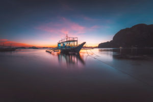 Corong beach, El Nido, Philippines. Soft glow sunset light over horizon on tropical beach with boat in ocean lagoon.