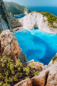 Navagio beach from top rocks at Zakynthos island, Greece. Stranded freightliner ship in unique beautiful blue lagoon and rocky mountains.