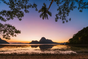 El Nido bay. Palawan, Philippines. Silhouette of palm trees in sunset light. Exotic tropical island in background.