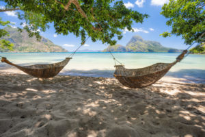 El Nido, Palawan, Philippines. Bamboo hammocks on shore in the shade. Beautiful tropical lagoon with epic Cadlao island in background.