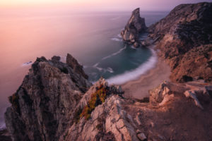 Travel to Praia da Ursa Beach, Sintra, Portugal. Landscape scene in lilac epic sunset light. Sharp cliffs and surreal coasty of Atlantic Ocean.