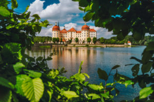 Castle Moritzburg in Saxony near Dresden. Framed by spring lush foliage leaves in foreground with reflection in pond Springtime. Germany.
