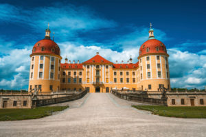 Castle Moritzburg located in Germany, Saxony region, near Dresden. Beautiful spring day with blue sky and white clouds. Surrounded by beautiful park.