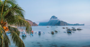 Panoramic scene of trip tourist boats in El Nido at evening sunset light. Palawan, Philippines. Cadlao island in background.