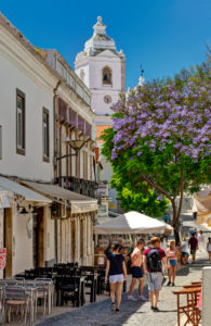 Lagos street scene in the old town with the church of Santo António and Jacaranda tree in flower