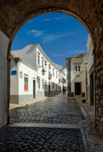 The arco da vila archway and cobbled street in the old town, Faro, the Algarve, Portugal