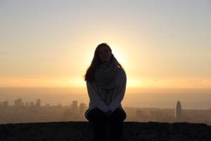 Junge Frau sitzt auf einer Mauer. Hinter ihr geht die Sonne über dem Meer und Barcelona auf.