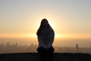Young woman sitting on a wall. Behind her, the sun rises over the sea and Barcelona.