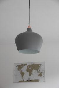 Pendelleuchte in grau mit einer Weltkarte im Hintergrund