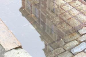 Spiegelung eines Hauses in einer Pfütze