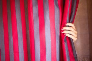 Hand an gestreiftem Vorhang