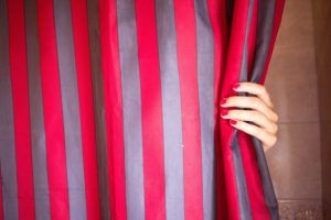 Hand on striped curtain