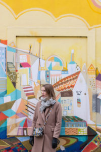 Young woman in front of colorful facade.