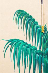 Palmenblätter an Hauswand gemalt