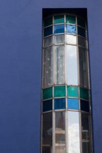 Rundes Fenster an blauem Haus.