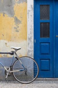Rennrad, Fassade und Tür im selben Farbschema