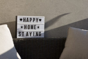 At home on the balcony, sign 'happy home staying'
