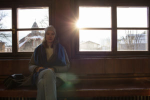 Frau vor Fenstern gegen die Sonne fotografiert
