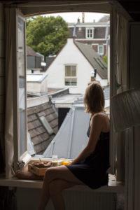 Junge Frau beim Frühstück auf der Fensterbank