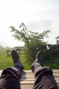 Hochgelegte Füße mit Schuhen im Garten