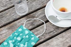 Leere Kaffeetasse und Mund-Nasen-Maske auf einem Holztisch