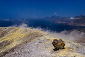 Italy, Sicily, Aeolian Islands, Vulcano, Gran Cratere, crater rim with fumaroles against Salina and Lipari